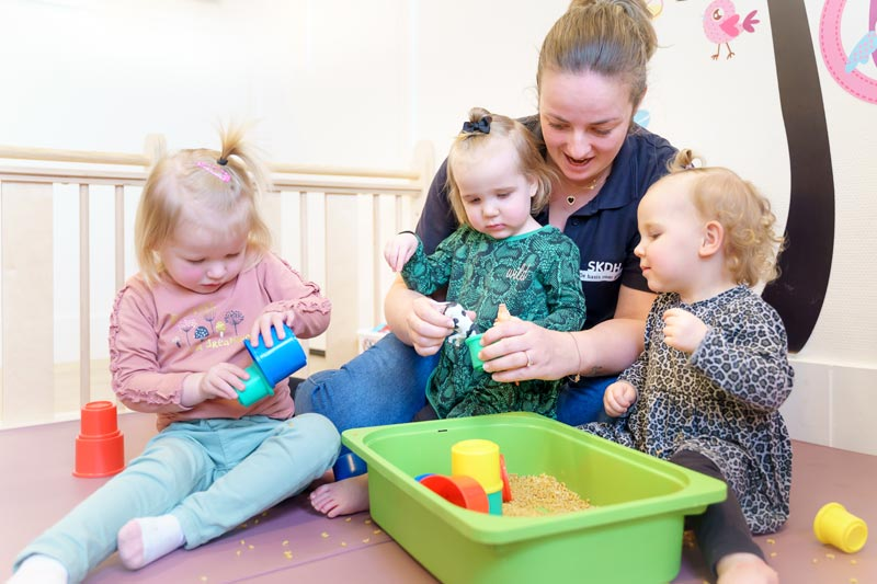 Begeleider met drie kinderen die een activiteit begeleidt - SKDH