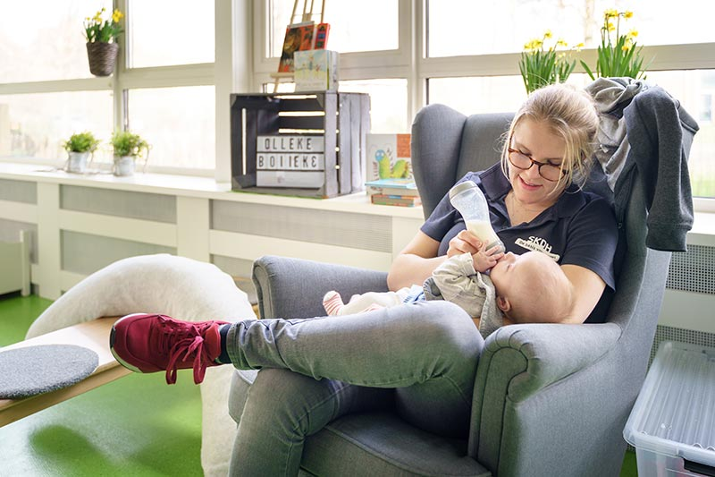 Kinderdagverblijf SKDH Verzorger geeft kind de fles
