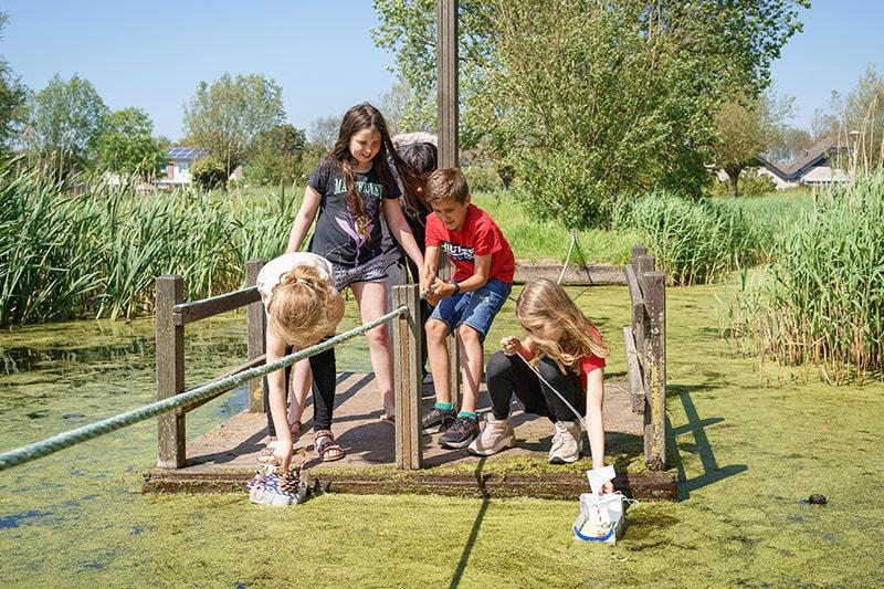 Kinderen testen zelf geknutselde bootjes