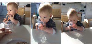 Kind drinkt zelfstandig uit doorzichtige beker