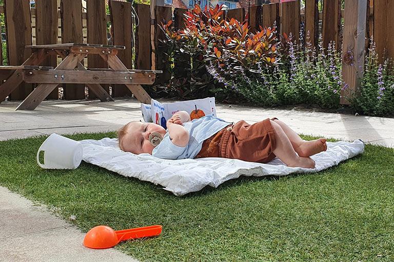 Baby op gras in tuin KDV de Tuimelaars