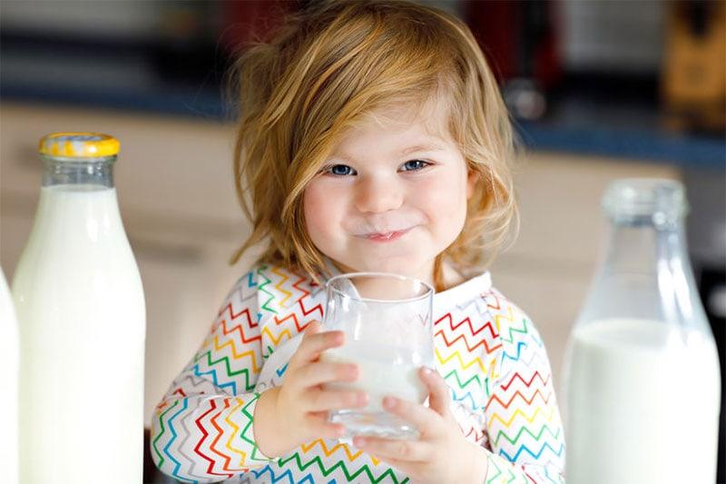 Kind drinkt melk uit glas